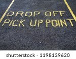 Small photo of Drop off pick up point parking space sign on black asphalt tarmac in large yellow letters