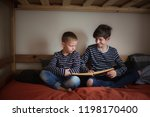 the brothers read together on... | Shutterstock . vector #1198170400