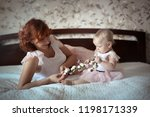 gentle red haired mother with a ... | Shutterstock . vector #1198171339