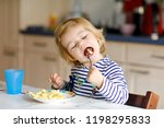 adorable baby girl eating from... | Shutterstock . vector #1198295833