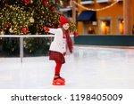 kids ice skating in winter park ...   Shutterstock . vector #1198405009