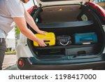 hands load bags in car trunk.... | Shutterstock . vector #1198417000