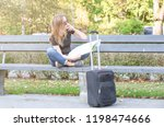 Small photo of confounded, lost or thinking tourist woman looking at map for right way, sitting on the bench in the park, luggage on the street