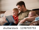 mid adult father is holding his ... | Shutterstock . vector #1198705753