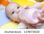Adorable Baby Girl is drinking milk from her bottle - stock photo