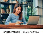 asian woman drinking coffee in  ... | Shutterstock . vector #1198735969