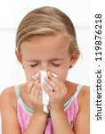 Little girl with the flu blowing nose - closeup - stock photo