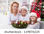 Christmas time - family around the advent wreath with all candles burning - stock photo