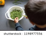 boy helps in the kitchen. cuts... | Shutterstock . vector #1198977556