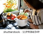 woman preparing a pumpkin soup | Shutterstock . vector #1199086549