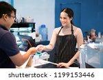 asian women barista accept... | Shutterstock . vector #1199153446