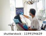 doctor dentist showing patient... | Shutterstock . vector #1199194639