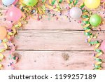 Small photo of Festival or carnival background in pastel vintage colors on a pink tinged wood background with a frame of streamers, balloons, confetti and candy around copy space
