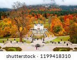 Tourists admire the scenery of majestic Linderhof Palace by a fountain pond in a baroque garden with colorful foliage of autumn forests on the foggy mountainside in background, in Bavaria, Germany