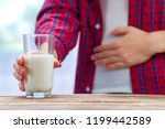 Small photo of A woman feels bad, has an upset stomach, bloating due to lactose intolerance. Dairy intolerant person. Health care concept. Lactose intolerance and dairy products