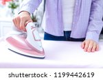 a young woman ironing clean... | Shutterstock . vector #1199442619