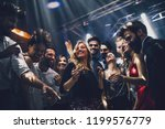 Stock photo shot of a young woman dancing in the nightclub 1199576779