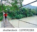 man walking on the suspension... | Shutterstock . vector #1199592283