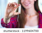Small photo of Attractive young woman holding a tampon. Critical days. Women's and gynecological health care. Hygiene. Menstrual cycle. Hygiene care during critical days. Tampon woman
