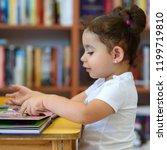 little girl indoors in front of ... | Shutterstock . vector #1199719810