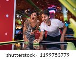 couple playing air hockey game... | Shutterstock . vector #1199753779