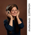 Music lover. Portrait of young smiling woman in headphones, dark brown background - stock photo
