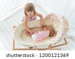 little girl and newborn baby in ... | Shutterstock . vector #1200121369
