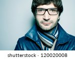 Portrait of a fashionable handsome man in blue jacket with striped scarf over light blue background. Close-up. Copy-space. studio shot - stock photo
