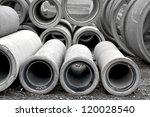 Heap of concrete pipes on construction site - stock photo