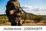 Hunter man. Hunting period, autumn season. Male with a gun. A hunter with a hunting gun and hunting form to hunt in an autumn forest. The man is on the hunt. Hunter with a backpack and a hunting gun.