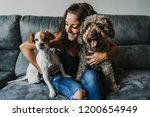 Stock photo young beautiful woman playing with her dogs in her sofa at home having fun together pet friendly 1200654949