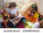 preschool teacher reading a... | Shutterstock . vector #1200854023