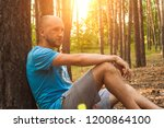 man sits in the woods with his... | Shutterstock . vector #1200864100