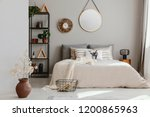 Stock photo round mirror and clock above bed with pillows in bright bedroom interior with flowers real photo 1200865963