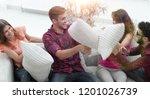 cheerful friends playing pillow ... | Shutterstock . vector #1201026739