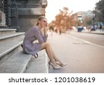 blonde woman sitting on stairs... | Shutterstock . vector #1201038619