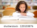 Young School Girl Reading A...