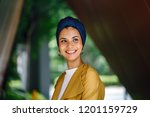 A close up portrait head shot of a young and attractive Malay Muslim woman in a turban (head scarf, hijab) in the city. She is smiling and beaming brightly.
