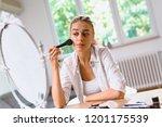 woman doing makeup at her home | Shutterstock . vector #1201175539