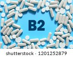 Small photo of Vitamin B2 text in white capsules frame on blue background. Pill with thiamine, thiamin. Dietary supplements and medication