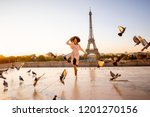 Small photo of Woman running on the famous square dispersing pigeons with great view on the Eiffel tower early in the morning in Paris