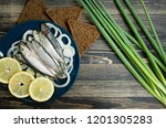 Stock photo small salted fish of baltic herring sprats on a wooden table top view 1201305283