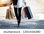 shopping bags were holding by... | Shutterstock . vector #1201436380