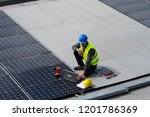 fitting photovoltaic panels on... | Shutterstock . vector #1201786369