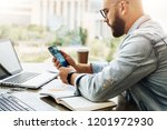 hipster man sits in cafe  uses...   Shutterstock . vector #1201972930