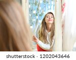 beautiful girl admires herself... | Shutterstock . vector #1202043646