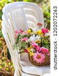 basket of flowers on a pile of... | Shutterstock . vector #1202072263