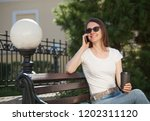smiling young woman sitting... | Shutterstock . vector #1202311120