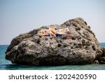A large rock with the Union Jack in Catalan Bay on the East side of the Rock of Gibraltar. Gibraltar is a British Overseas Territory located on the southern tip of Spain. - stock photo