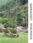 wooden deckchair on green grass. | Shutterstock . vector #1202446690